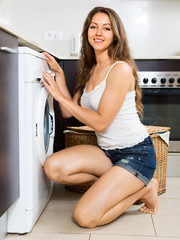 Smiling young girl washing clothes in washer