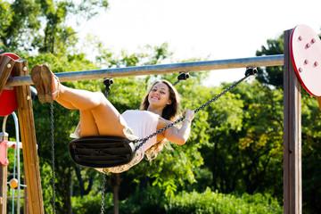 Happy  girl in skirt  on swing