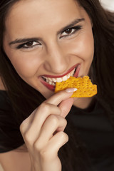 portrait of a smiling girl eating a cracker