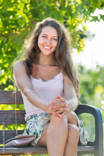 canvas print picture Young woman sitting on bench