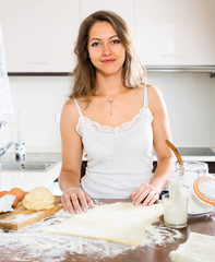 beautiful woman preparing cakes of dough