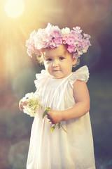 little girl in a wreath of phlox in the sun