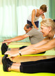 Instructor helps elderly to stretch