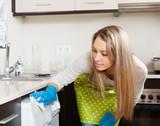 blonde woman cleaning washing machine