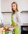 Happy  woman  in apron slicing vegetables