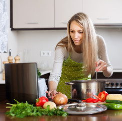 woman using notebook while cooking soup