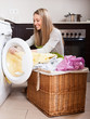 Happy blonde woman loading clothes into washing machine