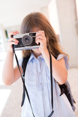 Girl shooting with a vintage camera
