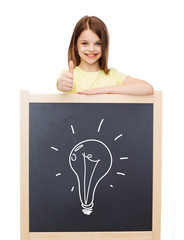 smiling girl with blackboard showing thumbs up