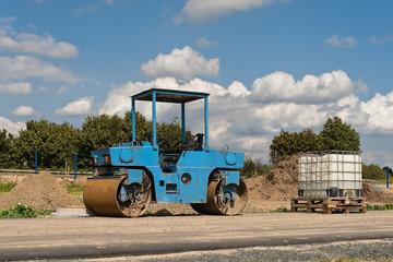 Eine alte blaue Strassenwalze und ein Tank für Bauwasser