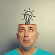 senior man looking up at light bulb