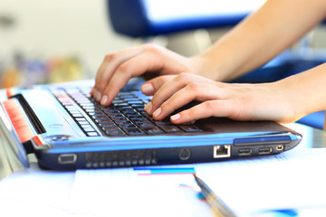 female learner typing on the laptop keyboard