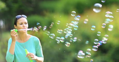 brunette girl blowing soap bubbles in sunlit park.