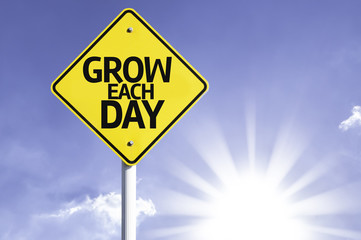 Grow Each Day road sign with sun background