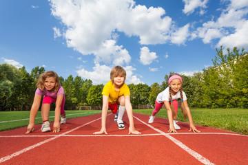 Smiling children on bending knees ready to run