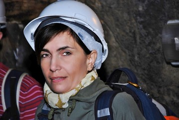 young woman inside the cave with a protective helmet