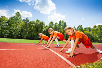 Children on bending knees in row ready to run