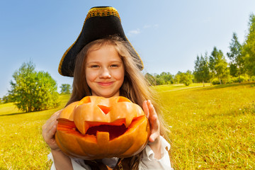 Halloween girl in costume of pirate holds pumpkin