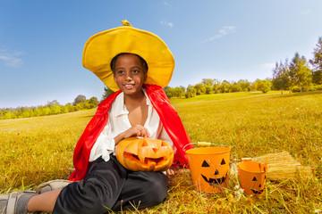 Halloween boy sits on yellow grass with pumpkin