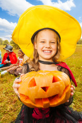 Girl in witch costume holds pumpkin with hands