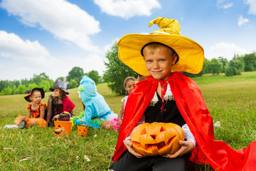 Boy in wizard costume holds Halloween pumpkin