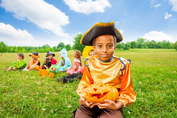 Smiling African boy in pirate costume and pumpkin