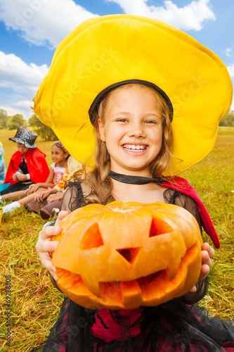 canvas print picture Girl in witch costume holds pumpkin with hands