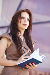 beautiful business woman on the street with blue notepad