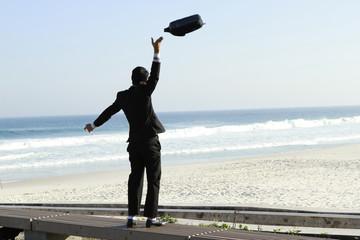 Business man throws bag of hand upward at the beach