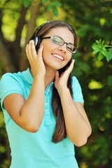 Portrait of young attractive girl listening to music with headph