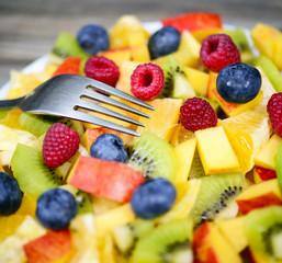 Macro shot of a fresh fruit salad with bananas kiwi orange blueb
