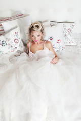 Romantic blonde woman lying in bed