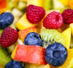 Macro shot of fresh fruit salad with bananas kiwi orange blueber