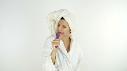 Woman singing in bathrobe after shower isolated