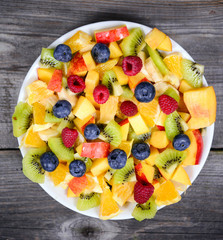 Top view of a fresh fruit salad with bananas kiwi orange blueber
