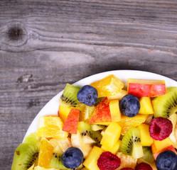 Top view of a fresh fruit salad with bananas kiwi orange blueber