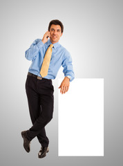 Businessman showing a blank sign while talking on the phone