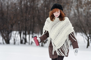 Young beautiful woman walking in winter park