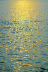 Golden sunlight reflection in the morning on the sea