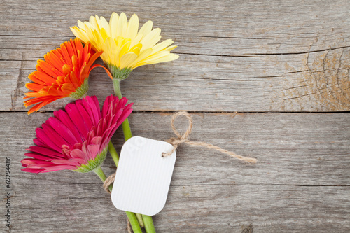 canvas print picture Three colorful gerbera flowers with tag