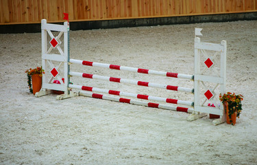 Red white obstacle for jumping horses. Riding competition.