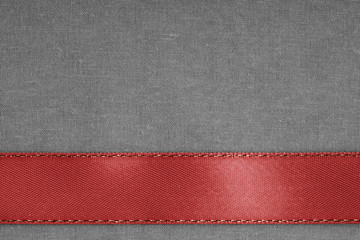 red ribbon on gray fabric background with copy space.