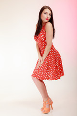 Full length pinup girl woman in retro red dress blowing a kiss