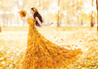 Autumn woman in fashion dress of fall maple leaves, artistic