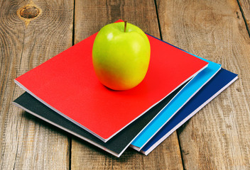 Apple and writing-books on wooden background.