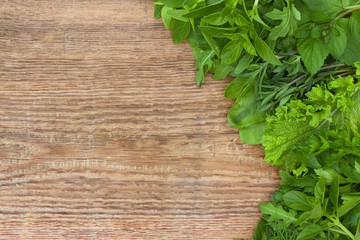 Fresh herbs on old wooden background