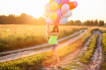 Beautiful happy young pregnant woman girl outdoors with balloons