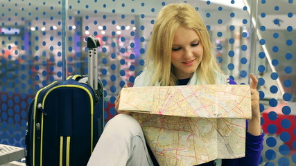 Girl reading map and smiling to the camera on the station