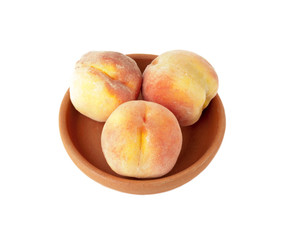 Three Ripe peaches in clay plate