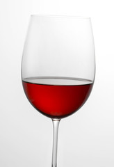 Glass half full of red wine